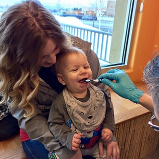 An infant who is visiting the dentist for the first time with our Richland pediatric dentist