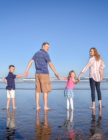 Dr. Morris holding hands with his family at the beach