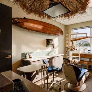Treatment room with a surfboard and a mounted TV from the ceiling
